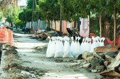 Sand in white plastic nylon bags on the street reconstruction site. Stock Images