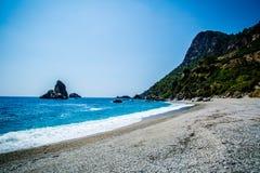 Sand, wild beach coast with sea or ocean and mountain rocks. Image stock photo
