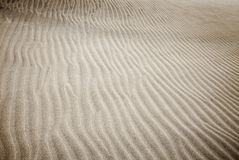 Sand and wind patterns. On dune surface. Pattern is formed by two types of sand grains - dark, small and lightweight and larger lighter and heavier ones stock images