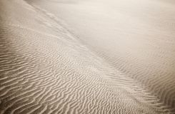 Sand and wind patterns. On dune surface. Pattern is formed by two types of sand grains - dark, small and lightweight and larger lighter and heavier ones royalty free stock photo