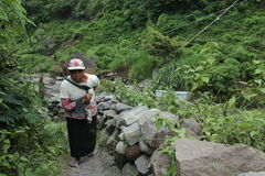 Sand woman. A woman carrying sand on basket after take this material from basic river on slove of Merapi Mountain Stock Image
