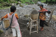 Sand woman. A woman carrying sand on basket after take this material from basic river on slove of Merapi Mountain Stock Photos