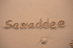 Sand. Words  sawaddee written in the sand with finger Stock Image