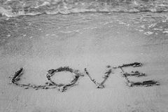 On the sand written word and his love washes wave, black and white Royalty Free Stock Images