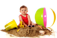 Sand is Yucky!. An adorable baby girl making a yucky! face while playing in a pile of sand with beach toys nearby. Isolated on white stock photography