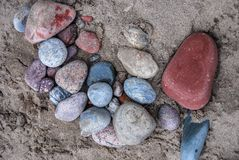 Sandabdeckungsstapel von recht collored Felsen stockfotos