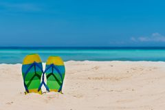 Sandal flipflops on a sandy ocean beach with blue sea and blue b. Ackground with copyspace. Tropical vacation concept stock image