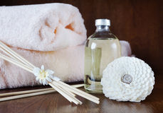 Sandal oil in a bottle and sticks for aromatherapy. On wooden surface Royalty Free Stock Photo
