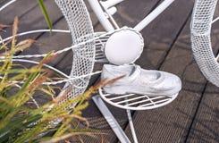 Sandalen der Kinder Metallsind- auf dem Pedal des Konzeptfahrrades Gartendekor in Form einer Sandale der Kinder Metall stockfotos