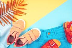 Sandalen, Turnschuhe, kurze Hosen und ein Zweig von Palmen auf einem modischen Hintergrund der gelb-blauen Farbe stockfotos