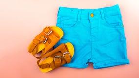 Sandalen und shortson ein rosa Hintergrund lizenzfreie stockfotos