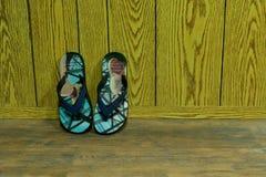 Sandaler & Flip Flops på trägolvet inom huset arkivbild