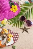 Sandaler, hatt, solglasögon och skal på sanden skal för hav för hav för bakgrundsstrandbegrepp Royaltyfria Bilder
