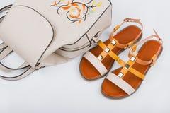 Sandaler och ryggsäck för ` s för trendiga kvinnor på vit bakgrund Royaltyfri Bild