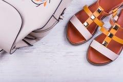 Sandaler och ryggsäck för ` s för trendiga kvinnor på vit träbakgrund Arkivfoto