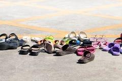 Sandaler skor många högen på jordning, massor av högsandalskor gummi, sandalskor, överhopar tillfälliga skor fotografering för bildbyråer
