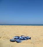 Sandales bleues dans le sable contre la mer et le ciel bleus Photo libre de droits