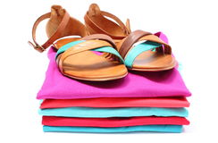 Sandales de femme sur la pile des vêtements colorés Fond blanc Image stock