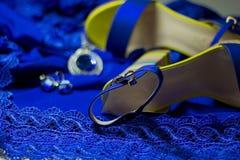 Sandales du ` s de femmes avec le talon haut sur le bleu de robe bleu avec les accessoires brillants Images libres de droits
