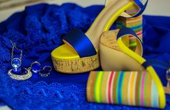 Sandales du ` s de femmes avec le talon haut sur le bleu de robe bleu avec les accessoires brillants Photo libre de droits