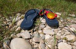 Sandales et lunettes de soleil en plastique avec la réflexion du soleil photos stock