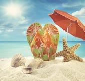 Sandales et étoiles de mer avec le parapluie à l'océan Image stock
