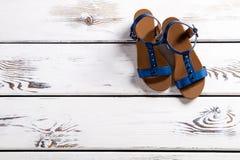 Sandales femelles sur l'étagère en bois Image libre de droits