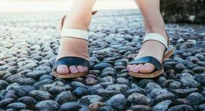 Sandales pendant les vacances : Les jambes de la femme portant des sandales images stock