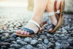Sandales pendant les vacances : Les jambes de la femme portant des sandales photos stock