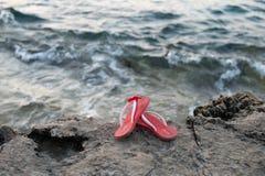 Sandales roses près de l'eau Photographie stock libre de droits