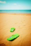 Sandales vertes sur la plage sablonneuse Photo libre de droits