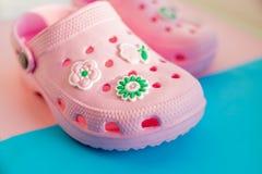 Sandali di gomma variopinti del ` s dei bambini sui precedenti blu scarpe di gomma rosa Scarpe del ` s dei bambini fotografia stock