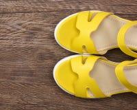 Sandalias amarillas de la cuña en superficie de madera oscura Imagenes de archivo