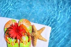 Sandalias coloridas con la flor y la toalla blanca Fotos de archivo libres de regalías