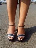Sandalias del negro del ` s de la señora con las tiras de plata foto de archivo