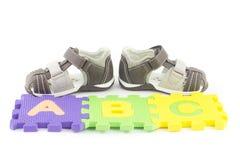Sandalias del niño y pedazos del rompecabezas del alfabeto Fotos de archivo libres de regalías