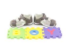 Sandalias del niño y pedazos del rompecabezas del alfabeto Imágenes de archivo libres de regalías