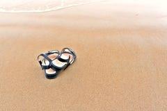 Sandalias del ` s de las mujeres en la playa Foto de archivo