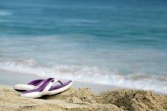 Sandalias en la playa Fotos de archivo