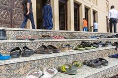Sandalias fuera de una mezquita durante tiempo del rezo en Dubai imagenes de archivo