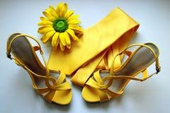 Sandalias, lazo y flor amarillos para casarse en el fondo blanco Imagenes de archivo