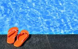 Sandalias por una piscina Imagenes de archivo
