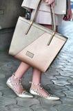 Sandalias que llevan jovenes de la mujer elegante del negocio con las correas y el bolso el sostenerse Imagen de archivo libre de regalías