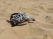 Sandalias que mienten en la arena en la playa Fotos de archivo libres de regalías