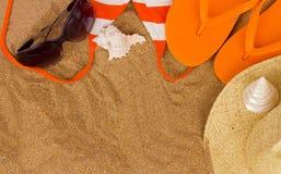Sandalias y accesorios anaranjados el tomar el sol en la arena Imagenes de archivo