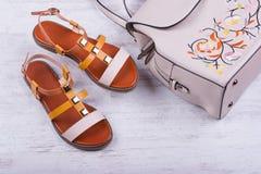 Sandalias y mochila del ` s de las mujeres de moda en el fondo de madera blanco Imágenes de archivo libres de regalías