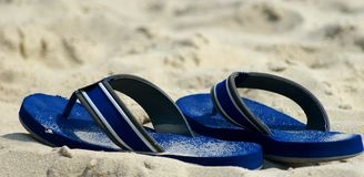 Sandals. Pair of blue sandals in the sand on the beach Stock Images