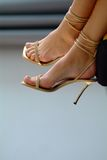 Sandals. Feet in golden high heels Royalty Free Stock Image