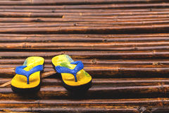 Sandals on the bamboo floor after raining. Used color tool for vintage tone Royalty Free Stock Image