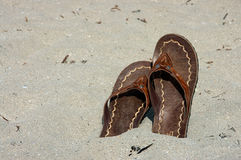 Sandals on the beach. Leather sandals on the beach Royalty Free Stock Photo